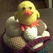 This cute baby chick sits on a pile of crocheted eggs.