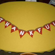 "Dody crocheted a pumpkin pie banner that says ""thankful""."
