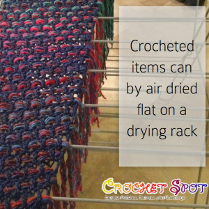 This is an example of a crochet shawl with fringe laid flat to dry.